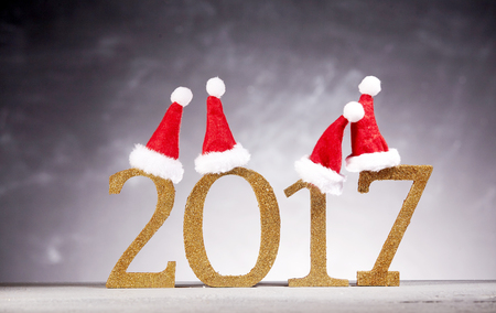 x mass: Four cute little red and white furry Santa hats on top of golden new year 2017 numbers over gray and white background