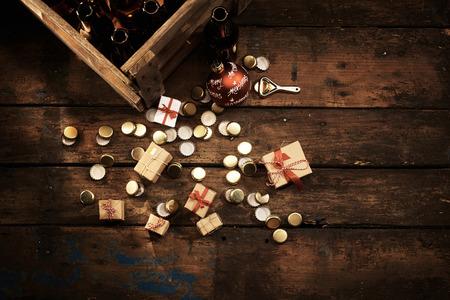 botellas vacias: concepto rústico o de país fiesta de Navidad con una caja de botellas de cerveza vacías y el abridor junto con una selección de regalos esparcidos mezclado con tapas de botellas usadas en los viejos tablones de madera oscura con espacio de copia