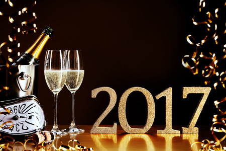 skoal: 2017 New Year celebration with a bottle and flutes of chilled champagne, golden party streamers and a modern clock counting down to midnight, copy space for your greeting Stock Photo
