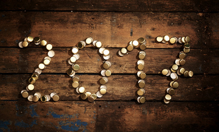 new year counter: 2017 date formed of used gold bottle tops on a rustic wood background with vignette for a conceptual New Years background