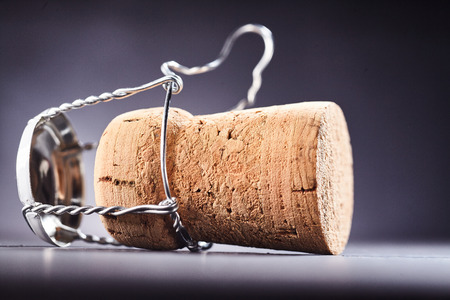 uncork: Loosened metal wire around wine bottle cork over dark background for concept about alcoholic drinks