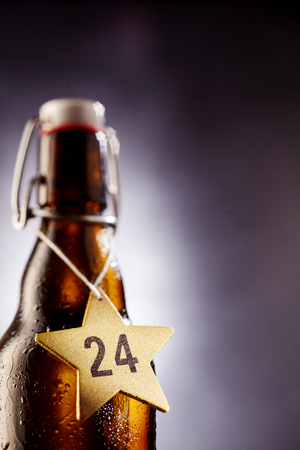 Selective focus view on number 24 in middle of star shape tag around glass bottle bottle used for wine