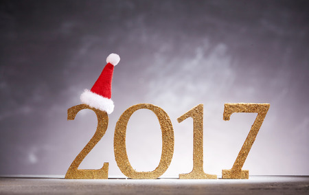 x mass: Golden new year in 2017 numbers decoration with hat perched on two over gray background