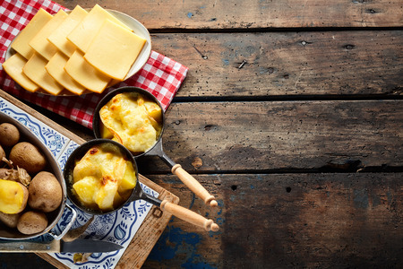 Delicious traditional Swiss melted raclette cheese on diced boiled or baked potato served in individual skillets, overhead view on rustic wooden table with copy space