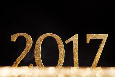 Simple gold glitter 2017 New Years Date over a sparkling pentagonal bokeh with a dark background with copy space for your greeting
