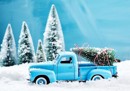 Oude blauwe vintage stuk speelgoed vrachtwagen met een Kerstboom die op de rug wordt geladen die door dikke sneeuw in een de winterbos drijven in een seizoengebonden stillevenscène Stockfoto