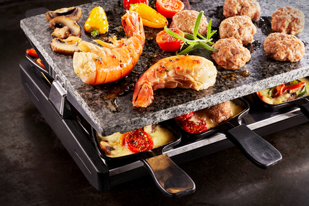 Spicy prawn tails and meatballs cooking with mushrooms and tomatoes over sizzling Swiss raclette cheese in skillets below , close up view Stock Photo