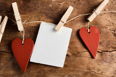 notelet: Rustic Valentines Day background with two red wooden hearts and a blank notelet hanging from clothes pegs on string over an old weathered wood panel Stock Photo