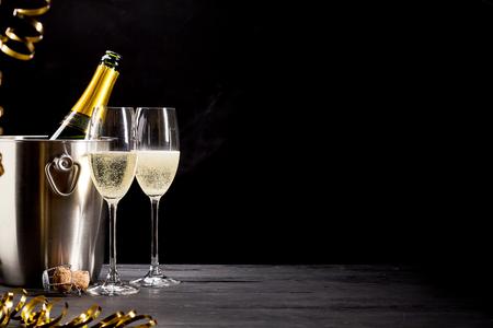 Funkelnder Champagner auf Eis für eine romantische Feier mit Goldpartyausläufern und eleganten Flöten des sprudelnden, Kopienraumes über einem dunklen Hintergrund