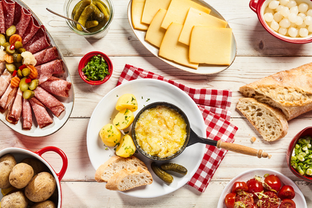 Delicious Swiss raclette cheese buffet with a platter of cold meats, pickles, potatoes, bread, salad, onions, herbs, and central skillet with melted raclette , overhead view on a rustic white table