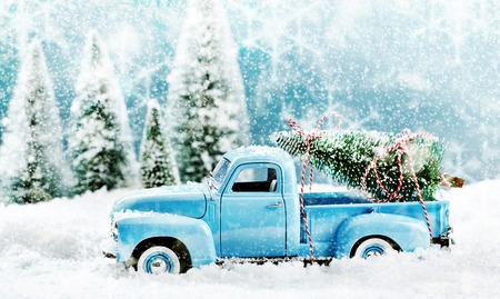 Vintage Spielzeug LKW holt einen Weihnachtsbaum aus einem Kiefernwald in einem Winter Schneesturm treibt durch dicken Schnee mit einem Baum auf den Rücken geladen, Seitenansicht saisonale Stillleben