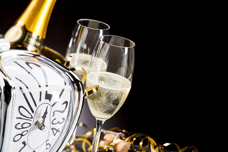 New Year background with a stylish modern clock counting down to midnight and chilled flutes of sparkling champagne with party streamers over a dark background with copy space