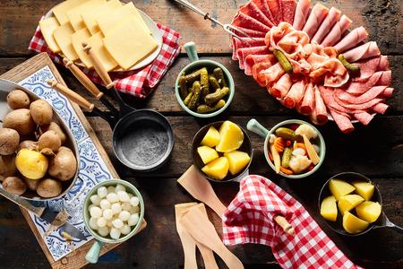 carnes y verduras: Presentación de ingredientes frescos para hacer raclette con un plato de embutidos, patatas, rodajas de queso y una variedad de verduras y suizos pepinillos cortados en cubitos, vista aérea