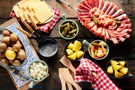 Presentation of fresh ingredients for making raclette with a platter of cold meats, potatoes, sliced Swiss cheese and assorted diced vegetables and pickles, overhead view Stock Photo