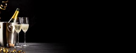 Bandiera festiva con champagne romantico in due flauti eleganti a fianco di una bottiglia agghiacciante sul ghiaccio su uno sfondo panoramico scuro con spazio di copia Archivio Fotografico - 67055163