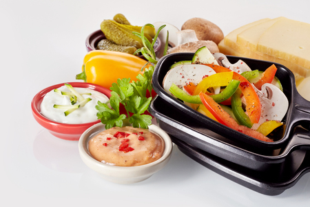 cream cheese: Healthy fresh ingredients for making raclette with slices of Swiss cheese, dips, freshly diced sweet peppers and mushrooms, herbs, pickles and potatoes.