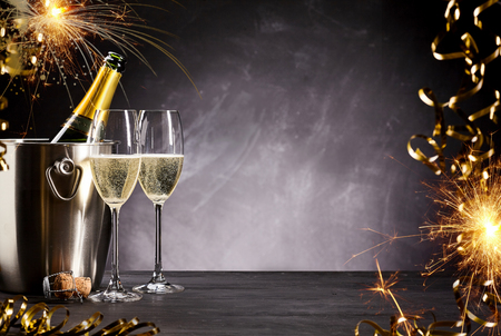 Romantic celebration with sparklers, party streamers and flutes of champagne alongside a bottle on ice with a smoky atmospheric background and copyspace Stockfoto
