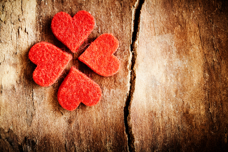 Textured romantic red hearts forming an Irish shamrock or lucky four leaf clover on old dried cracked wood background with copy space for your Valentines message Stock fotó