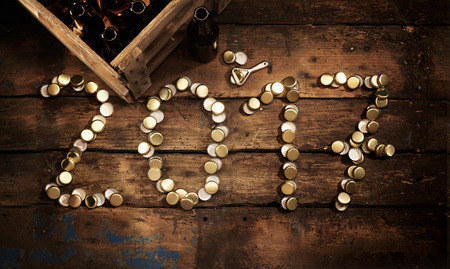 year old: 2017 rustic New Year party celebration with the date formed of used gold bottle tops alongside a crate of empty beverage bottled and opener viewed from above with a heavy vignette on old vintage wood
