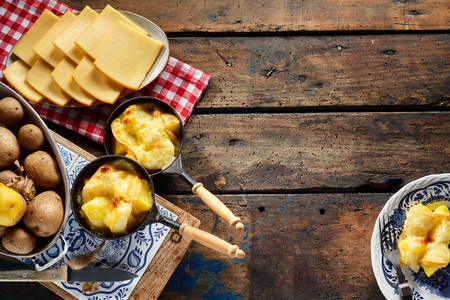 Regional Swiss cuisine with raclette cheese melted over fresh boiled potatoes in an overhead side border view with ingredients and prepared servings on rustic wood with copy space Фото со стока