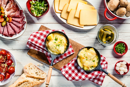 Delicious restaurant dinner with Swiss raclette cheese sliced and melted on potato served with cold meats, bread, pickles and herbs on rustic red and white napkins over a white wood table, top view Фото со стока