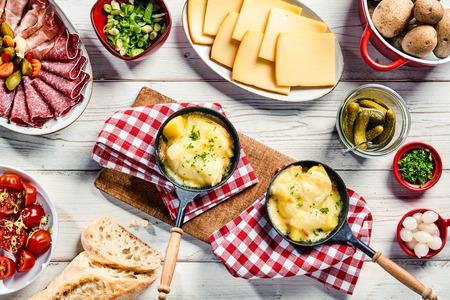 Heerlijk restaurant diner met Zwitserse raclette kaas gesneden en gesmolten op aardappel geserveerd met vleeswaren, brood, augurken en kruiden op rustieke rode en witte servetten over een witte houten tafel, bovenaanzicht