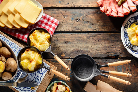 Traditional regional Swiss cuisine with melted raclette cheese over boiled potatoes served with cold meats, rustic border of the ingredients and skillets with copy space Banco de Imagens