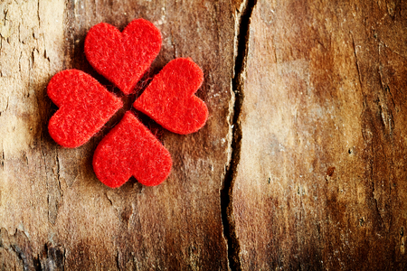 Four bright red hearts forming a lucky shamrock or four-leaf clover symbolic of love, romance and Valentines Day on an old grunge wood surface with large crack and copy space