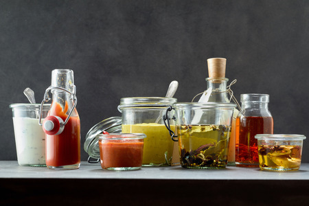 catsup bottle: Front view on catsup, mustard and food condiments on dark table. Stock Photo