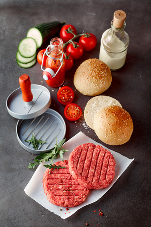 High Angle View of Raw Beef Hamburger Patties, Press, Bread Rolls with Sesame Seeds, Fresh Vegetables and Homemade Sauces on Dark Gray Stone Textured Counter Surface
