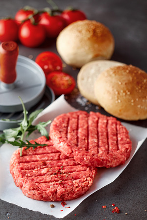 Two Raw Beef Hamburger Patties on Textured Gray Stone Counter with Hamburger Press, Bread Rolls Topped with Sesame Seeds and Fresh Tomatoes