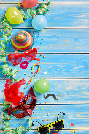 Various colorful streamers, balloons, candy and masquerade objects on faded blue wooden paneling.