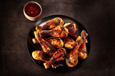 chilies: Plate of grilled spicy chicken legs served ready for a finger buffet with a side dish of hot chili sauce, overhead view on a slate background Stock Photo