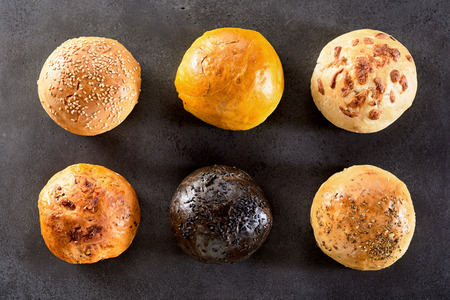 High Angle View of Variety of Six Hamburger Buns or Dinner Rolls Arranged in Two Rows on Textured Table or Counter Surface Stock Photo