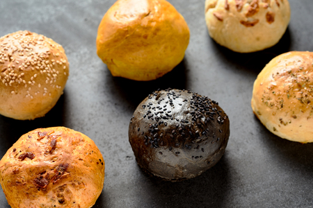 High Angle Close Up View of Various Hamburger Buns or Dinner Rolls Arranged in Two Rows on Stone Textured Table or Counter Surface