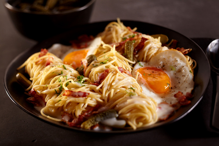 Delicious breakfast of bacon and egg spaghetti dish close up in dark plate. Includes pickle garnish. Stock Photo