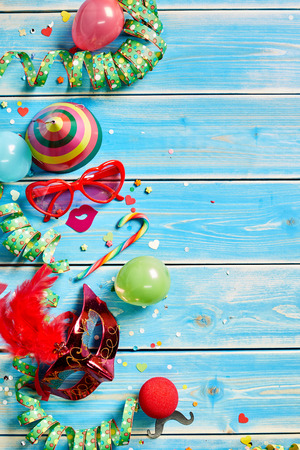 party favors: Various colorful streamers, balloons, candy and party favors on faded blue wooden paneling.