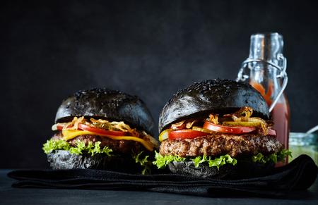 ajonjoli: Dos deliciosas hamburguesas grandes bollo negro con lechuga, cebolla y tomate al lado de botella de ketchup detrás de ellos