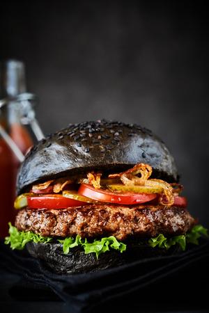 an onions: Close up en sándwich de hamburguesa negra rellena con lechuga, cebollas fritas y rodajas de tomate