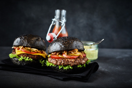 freshly prepared: Two freshly prepared large pumpernickel bun hamburgers with lettuce, onion and tomato on black folded napkin beside ketchup and mustard containers