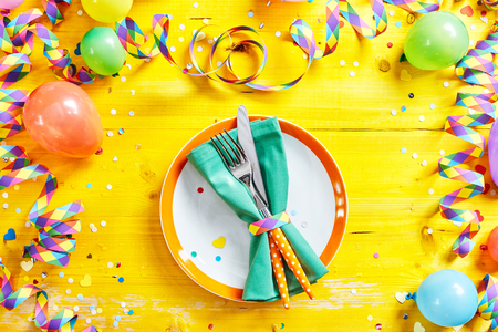 fasching: Carnival or Fasching cutlery and plate with fork and knife in overhead view on yellow party or birthday background table