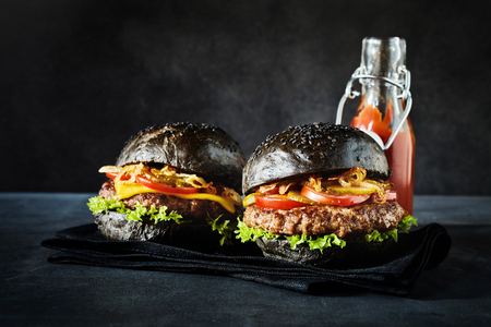 ketchup bottle: Pair of ready to eat large black bun hamburgers with ketchup bottle behind them
