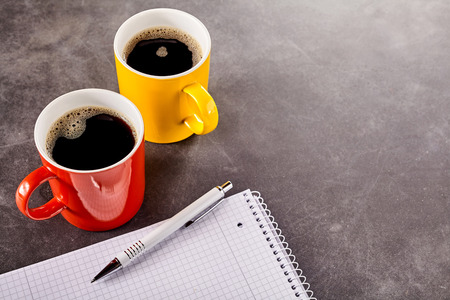 energising: Red and yellow mugs filled with black coffee on the dark table surface with white pen over notepad