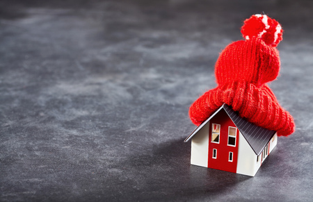 lagging: Small toy house with red knitted hat on its roof standing isolated over dark surface