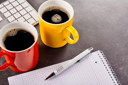 energising: Close-up of workspace with two mugs of coffee, white keyboard, pen and blank notebook on gray desk