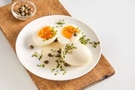 caper: Healthy free range eggs in savory caper and mustard sauce garnished with fresh herbs and served on a wooden chopping board, high angle view with copy space