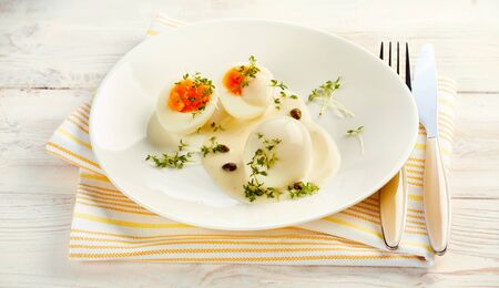 caper: Delicious free range healthy hard boiled eggs in mustard and caper sauce garnished with fresh herbs and served on a white wooden table on a napkin