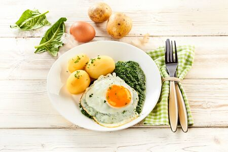 Fried egg, creamy pureed spinach and baby potatoes garnished with chopped parsley on a rustic white wooden table with fresh ingredients behind and a napkin with utensils