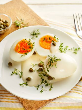 caper: Tasty appetizer of boiled free range eggs served with caper and mustard sauce topped with a sprinkling of fresh herbs, close up high angle view on a white plate and wooden cutting board