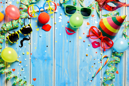 Colorful carnival frame of bright photo booth accessories, streamers, party hat and confetti on rustic blue wooden planks with central copy space